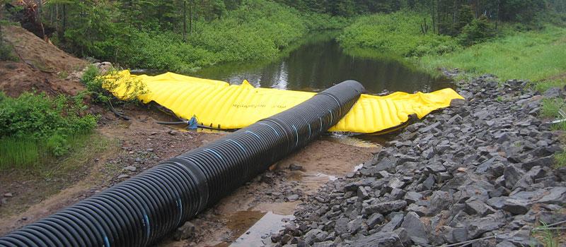 Elastyczne grodzice Water-Gate © do pracy w rzekach. Wyjmowana tama z obejściem na rurociągu.