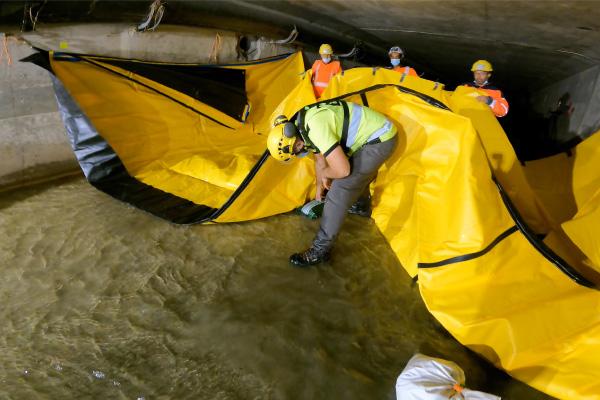Umieść worki żwiru na ziemi pod elastyczną zaporą Water-Gate ©, aby zwiększyć siły tarcia.
