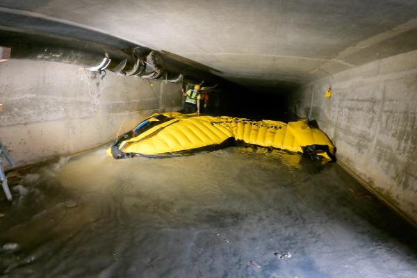 Usunięcie elastycznej grodzy Water-Gate ©. Krawędź natarcia jest podniesiona, aby przepuścić wodę pod grodą i zmniejszyć siły tarcia.